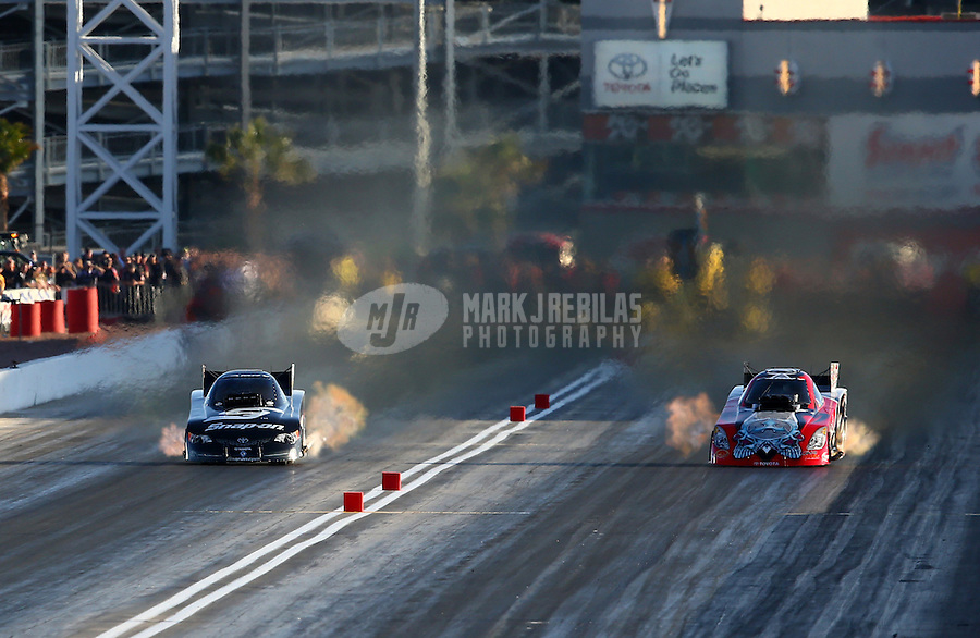 Mar 28, 2014; Las Vegas, NV, USA; NHRA funny car driver Cruz Pedregon (left) races alongside Chad Head during qualifying for the Summitracing.com Nationals at The Strip at Las Vegas Motor Speedway. Mandatory Credit: Mark J. Rebilas-