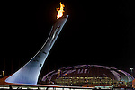 Olympic flame burning against a night sky and Bolshoy Ice Dome during the 2014 Sochi Olympic Winter Games at the Olympic Park on February 8, 2014 in Sochi, Russia. Photo by Victor Fraile / Power Sport Images