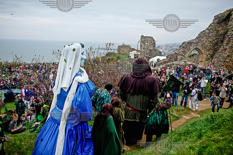 People gather at a Jack in the Green festival. The festival is part of a recent revival of an older custom where people would wear frameworks covering much of their bodies which were decked out in foliage. The custom is connected to English May Day parades that herald  the coming of summer.