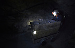 A miner moves an ore cart inside a mine in Potosi, Bolivia. The mine produces silver and other metals.