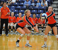 NWA Democrat-Gazette/ANDY SHUPE<br /> Lindsay Glynn (4) and Elleson Dunagin of Rogers Heritage reach to dig a ball against Springdale Har-Ber Thursday, Sept. 17, 2015, at Wildcat Arena in Springdale. Visit nwadg.com/photos to see more photographs from the game.