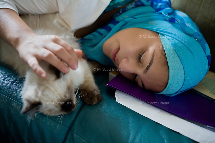 """Shayreen, 16, takes a break from her summer homework to play with a kitten at her home in West Warwick, Rhode Island, USA, on Sunday, Aug. 22, 2011.  """"You are more exciting that homework,"""" she told the cat. The family has two adult cats and and two kittens.  Unlike the rest of her family, Shayreen is very devoted to her Muslim faith.  """"I feel it's my responsibility as a Muslim to be a positive role model,"""" said Shayreen, """"I see a negative energy toward Muslims in the media.""""  Shayreen is will be a high school junior at Lincoln School, an all-girls Quaker school in Rhode Island. The rest of her family is not particularly religious.  When Shayreen began wearing the hijab head covering in her early teens, """"My parents were very supportive, but my aunt tried to talk me out of it. My grandmother was upset.  I was more worried about what my family would think [than what other people would think].""""..photo by: M. Scott Brauer for Education Week"""
