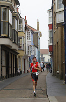 27 JUL 2013 - CROMER, GBR - Sam <br /> Kingston makes his way down a narrow side street on the run during The Anglian Triathlon in Cromer, North Norfolk, Great Britain (PHOTO COPYRIGHT &copy; 2013 NIGEL FARROW, ALL RIGHTS RESERVED)