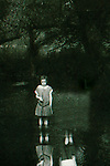 A child in the countryside standing beside a pond with reflection of second girl