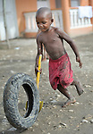 A boy rolls a tire along a street in Batey Bombita, a community in the southwest of the Dominican Republic whose population is composed of Haitian immigrants and their descendents.