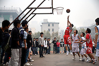 University students play basketball on the campus of the Nanjing University of Traditional Chinese Medicine in Nanjing, China.
