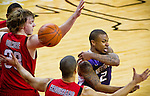 The University of Washington Huskies guard Isaiah Thomas delivers a no-lookpass through Seattle University Redhawks defenders at Key Arena in Seattle Tuesday, Feb. 22, 2011. (Photo by Andy Rogers/Red Box Pictures)