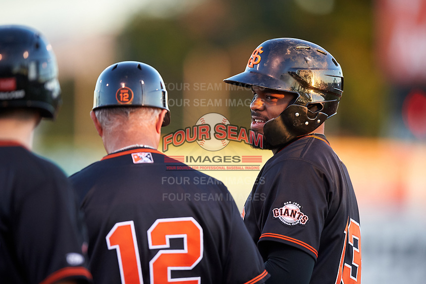 San Jose Giants center fielder Heliot Ramos (13) talks to first base coach Gary Davenport (12) during a California League game against the Visalia Rawhide on April 12, 2019 at San Jose Municipal Stadium in San Jose, California. Visalia defeated San Jose 6-2. (Zachary Lucy/Four Seam Images)