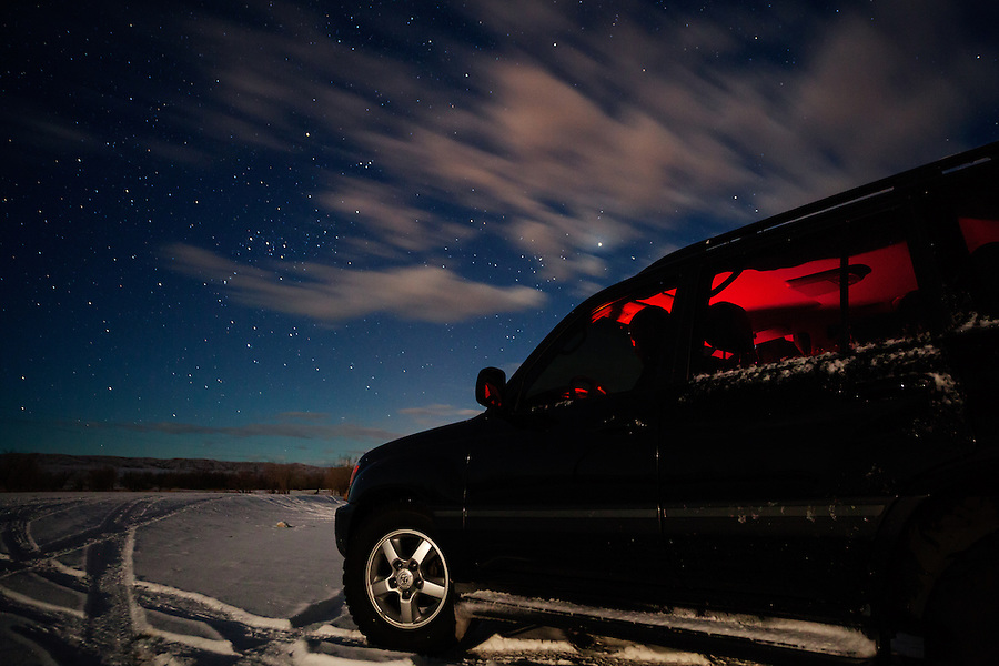 A man reads a map inside of a 2004 Toyota Land Cruiser with red interior lights under a starry sky in Wyoming.