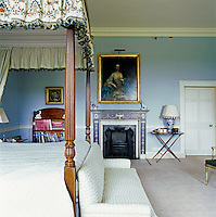 The master bedroom is decorated with a formal portrait  above the fireplace