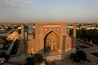 Aerial view of the Sher-Dor Madrasah, 1619-1636, Samarkand, Uzbekistan, pictured on July 15, 2010 at sunset which lights up the elaborately tiled facade and domes. In the background is the Chorsu, a dome-arched construction, 15th and 18th century, the old shopping centre of the city. Samarkand, a city on the Silk Road, founded as Afrosiab in the 7th century BC, is a meeting point for the world's cultures. Its most important development was in the Timurid period, 14th to 15th centuries.