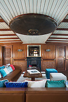 The sitting room on the middle deck is furnished with leather banquettes and lined with carved wood panelling and is dominated by a handmade Moroccan ceiling light.  Doors either side of the central fireplace open into the adjacent dining saloon