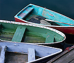 Rockport, Cape Ann, MA<br /> Three painted wooden skiffs on the wharf at Rockport Harbor