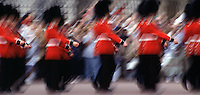 Blurred motion image of Buckingham Palace Guards in traditional uniforms marching in parade formation as tourists look on. London, England.