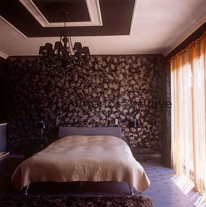 A brown and neutral bedroom with a patterned wallpaper on one wall. A chandelier with brown shades hangs above a double bed with a neutral cover.