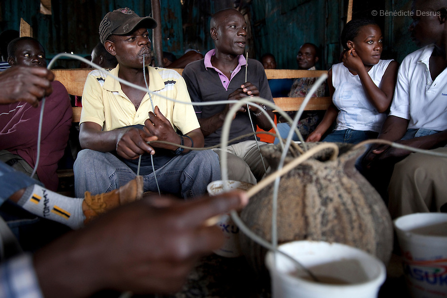 People drink Busaa, a traditional fermented beer, at Madiaba Busaa club at midday in a Nairobi slum on April 21, 2013. Busaa is made by crudely fermenting maize, millet, sorghum or molasses. At Kshs 35 per liter it is much cheaper than a Kshs120 half-liter bottle of commercial beer. The local brew was legalised in 2010 and since then Busaa clubs have become increasingly popular in slums and rural areas. Drinking is on the rise in Kenya, especially among young people. Photo by Benedicte Desrus