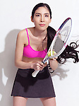 Young Japanese woman with a tennis racquet wearing a sporty outfit on white background