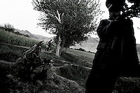A villager from Kawati Atis directs US ARMY soldiers form battle company, 503d regiment, 173d airborne brigade, to a mosque close to a compound in which a large stash of taliban ammunition should be in the Kawati Atis village in the Zabul province of southern Afghanistan on sept 06 2005..the villager was hand cuffed for security reasons being the area densivly active with taliban fighters..US intelligence had spotted 12 taliban in the village of Zinde. After 4 hours of intense exchange of fire and use of air support Apache gunships and A10 aircrafts 08 talibans were killed, one was captured and one ran away..On September 06 the same unit was moved to a different location where a Taliban commander, N16 on the US most wanted list for Afghanistan was supposed to be hiding. He was not found. In the afternoon the unit was moved to the village of Kawati Atis where a stash of weapons was supposed to be hidden in a compound. The raid lasted for 5 hours, involving a 3km movement trough a valley. The unit occupied the