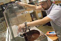 NWA Democrat-Gazette/CHARLIE KAIJO Bar Manager Michael Day checks on a batch of lavender chocolate in a temperer machine, Saturday, July 6, 2019 at Markham & Fitz Chocolate in Bentonville. The machine is used to temper the chocolate and make it more crispy, shiny and harder he said. <br /> <br /> Markham & Fitz Chocolate held a World Chocolate Day event showcasing chocolate samples from around the world.