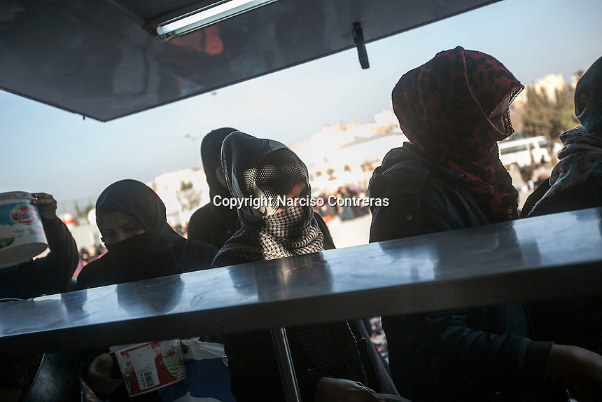February 15, 2016: Syrian refugee women line up as they receive for food distribution at one neighbourhood in the outskirst of Kilis border town. The Kimse Yok Mu, a Turkish NGO, set up a kitchen to provide free meals to the thousands of refugees that have arrived from the war-torn Syria.