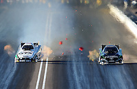 Feb. 22, 2013; Chandler, AZ, USA; NHRA funny car driver John Force (left) hits the center line timing blocks alongside Alexis DeJoria during qualifying for the Arizona Nationals at Firebird International Raceway. Mandatory Credit: Mark J. Rebilas-