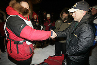 Doug Swingley finishes the Iditarod in 2nd place at the finish line in Nome and is congratulated by winner Jeff King