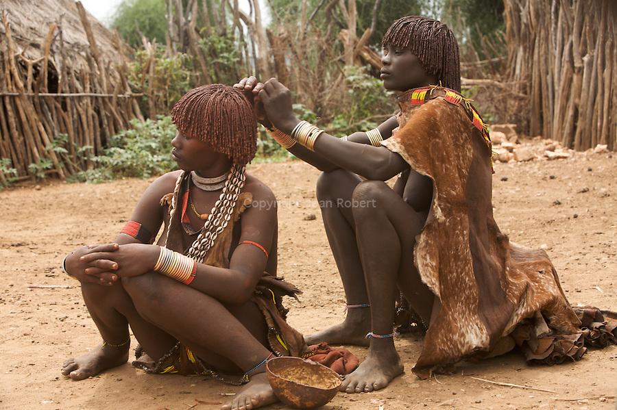 Les femmes Hamer enduisent leurs fines tresses d'ocre rouge mélé d'huile. village de Lojira à côté de la ville de Turni