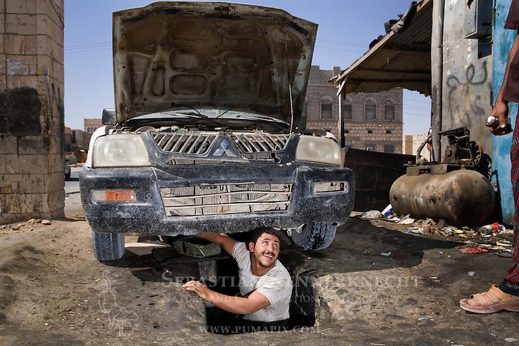 Mechanic looking out from under car, Al Ghaydah, Yemen