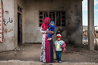 IRAK, Bashika: Anqam is posing with her 2 children in front of their house that was damaged during the offensive against Daesh. Members of Daesh were occupying this house of this small village, Derek, near the city of Bashika, the 11th December 2016. <br /> <br /> IRAK, Bashika: Anqam pose avec ses 2 enfants devant leur maison qui a &eacute;t&eacute; endommag&eacute;e lors de l'offensive contre Daesh. Des membres de Daesh occupaient cette maison de ce petit village, Derek, pr&egrave;s de la ville de Bashika, le 11 d&eacute;cembre 2016.