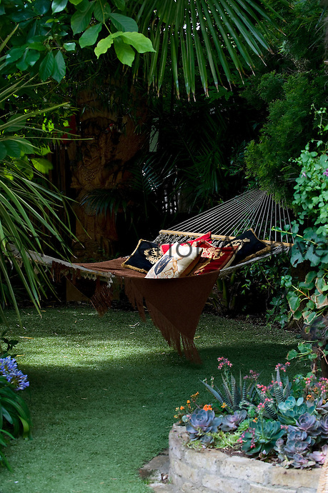 A large hammock covered with a throw and cushions in a sunlit spot in the garden