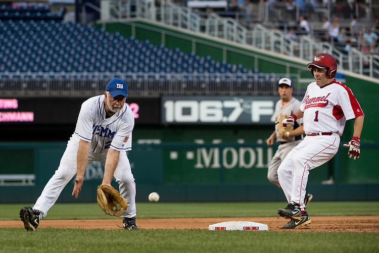 UNITED STATES - JUNE 25: Rep. Tim Bishop, D-N.Y., waits for a low throw from home as Rep. Steve Scalise, R-La., runs to third base during the Roll Call Congressional Baseball Game on Wednesday, June 25, 2014. (Photo By Bill Clark/CQ Roll Call)