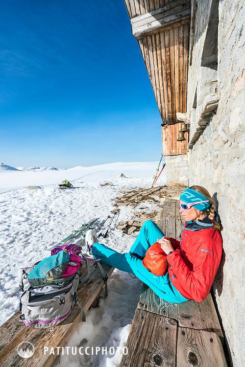 A ski tour through the Pirin Mountains of Bulgaria. Outside the Tevno Ezero Hut a woman sits organizing her ski gear.