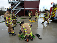 NWA Democrat-Gazette/ANDY SHUPE<br /> Kevin Sbanotto, left, and James Quinton, both with the Fayetteville Fire Department, roll a firehose Wednesday, March 13, 2019, while working on high rise firefighting training at the department's training facility in south Fayetteville. City voters will head to the polls April 9 to consider 10 bond questions totaling more than $226 million in projects. About $15 million is included for the Fire Department for three new fire stations, trucks and equipment.