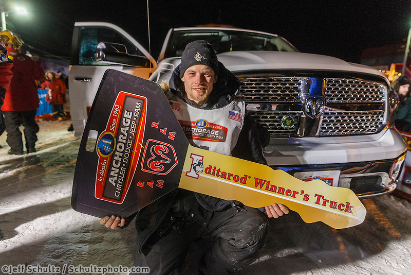Dallas Seavey recieves the key to his new Dodge pickup truck under the burl arch after winning the 2014 Iditarod in Nome on Tuesday, March 11.  Iditarod Sled Dog Race 2014.<br /> <br /> PHOTO (c) BY JEFF SCHULTZ/IditarodPhotos.com -- REPRODUCTION PROHIBITED WITHOUT PERMISSION