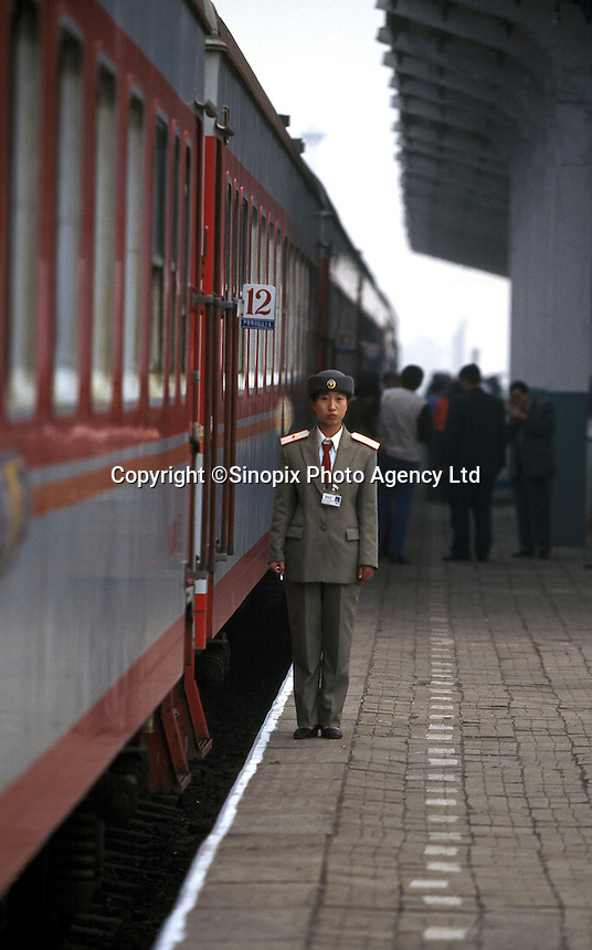 A conductor stands on platform next to the Beijing to Hong Kong long-distance train, Beijing, China.