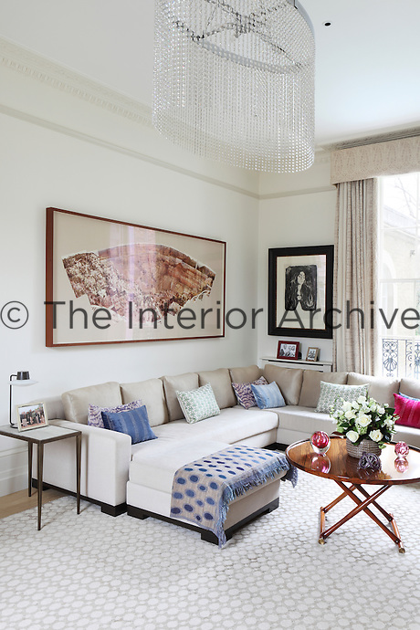 A collage of photographs depicting the Grand Canyon hangs above the L-shaped sofa in the living room