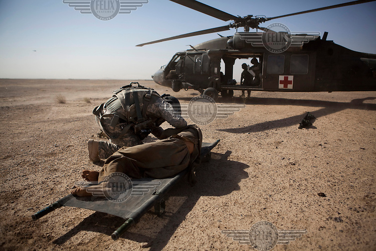 Sgt Shields, a medic from Charlie Company, Sixth Battalion, 101st Aviation Regiment treats a wounded civilian next to a US Army medevac helicopter after his vehicle hit an IED (improvised explosive device) near Kandahar.