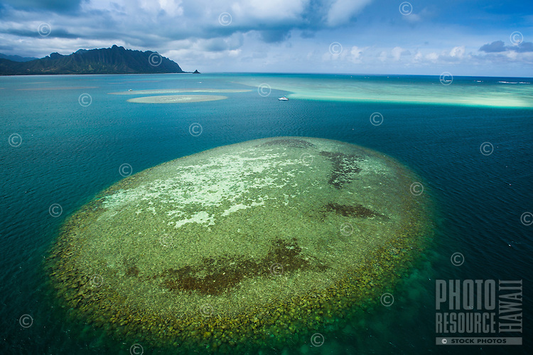 An aerial view of reef formation near Windward O'ahu's Kane'ohe Sandbar, with Chinaman's Hat in the far distance.