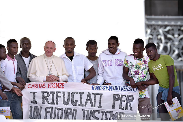 Pope Francis poses surrounded by a group of refugees  during of a weekly general audience at St Peter's square in Vatican. on June 15, 2016