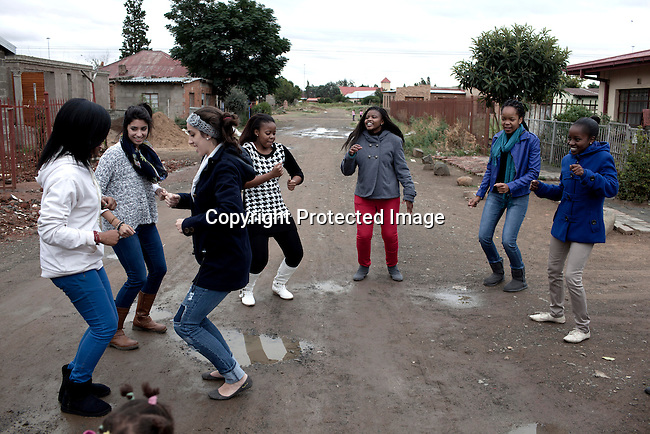 BLOEMFONTEIN, SOUTH AFRICA APRIL 20, 2013: Students from the University of the Free state in Bloemfontein hang out in a black township outside Bloemfontein, South Africa. The black students invited their white friends to enjoy the township, eat the local food and they hospitality. Pinky Mokemane (in blue jacket) a student who was racially attacked by white students. Photo by: Per-Anders Pettersson