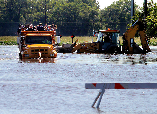 Employees and customers are evacuated from Wal-Mart in a dumptruck and front end loader during flooding in Ames, Iowa, August 11, 2010.
