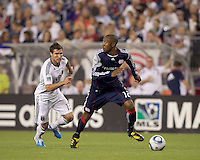 New England Revolution defender Cory Gibbs (12) in his defensive zone looks to pass as DC United forward Chris Pontius (13) pressures. The New England Revolution defeated DC United, 1-0, at Gillette Stadium on August 7, 2010.