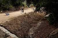 """Ventura, California, July 23, 2010 - Tim 'Timbow' Bowman rides his bike along the paths of the Ventura River bottom where he has been living in a tent since the early 1990's. In 1987 Bowman's 18-month-old daughter, Miranda Laurel, died from Lyme disease. His wife left him soon afterwards. A year later he fell through a plate glass window while working on a construction site, leaving him disabled and unable to work construction. He says the loss of his wife and daughter and his struggles with work sent him into a spiral. He eventually lost his home. He says he lives in the 300+ community along the river bottom because he """"feels at home."""" Adding, """"I feel loved down here. Up there is nothing but trouble."""" The two-mile stretch of river bottom from the Pacific to Stanley Road is home to about 300 homeless, who have carved tunnels and paths into the tall grass and bamboo. Bowman, who survives off of SSI, says, """"I lead an honest life. I don't steal, I don't rob and I share whatever I can."""" .."""