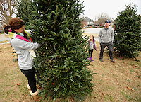 STAFF PHOTO ANDY SHUPE - Elda Scott of Rogers, left, holds a Christmas tree as her daughter, Amelia, 6, and husband, Eric Scott, check it over as they shop for a tree at the Rogers Optimist Club's annual Christmas tree lot Sunday, Dec. 7, 2014, in downtown Rogers. The lot is open seven days a week and raises money for local activities, funds and scholarships.