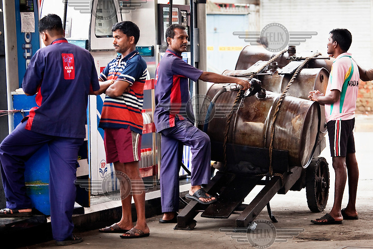 A man fills drums with fuel at a petrol station. His business is to then pull the cart carrying the drums to areas where people are willing to buy fuel.