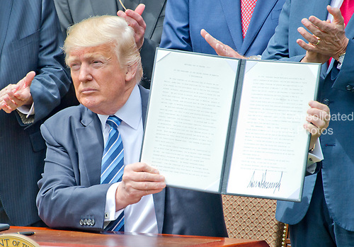 United States President Donald J. Trump signs a Proclamation designating May 4, 2017 as a National Day of Prayer and an Executive Order &quot;Promoting Free Speech and Religious Liberty&quot; in the Rose Garden of the White House in Washington, DC on Thursday, May 4, 2017.<br /> Credit: Ron Sachs / CNP