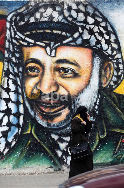 Palestinians walk in front of a mural of late Palestinian leader Yasser Arafat in Gaza City on November 27, 2012. The body of Arafat was exhumed, eight years after his death, as part of an investigation into allegations he was poisoned. Photo by Ashraf Amra