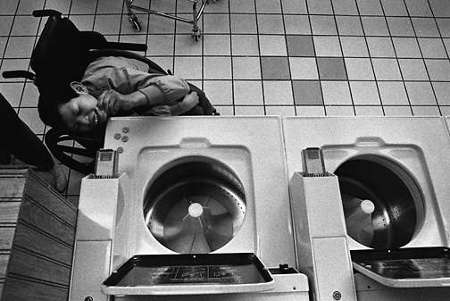 Despite his severe multiple handicap (SMH) disabilty Chava Mendoza of Serramonte High School nimbly puts coins into a washing machine at a laundromat in Daly City, California.  (photo by Pico van Houtryve)