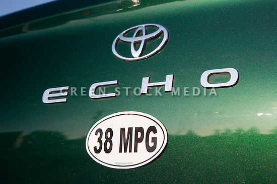 Close up of a 38 miles per gallon fuel efficiency bumper sticker on a green Toyota Echo car. Sticker from MPG Stickers (mpgstickers.com), a grassroots, nonprofit campaign which aims to accelerate the adoption of fuel efficient vehicles in the United States. California, USA. Property released from mpgstickers.com.