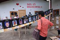 """MEDELLÍN - COLOMBIA, 07-06-2014. Una mujer ve las imágenes con los nombres de las personas desaparecidas en """"La Escombrera"""", en la Comuna 13 de Medellín, durante una vigilia contra las desapariciones forzadas. En 2002, Medellín fue sacudido por la violencia después de la decisión del Gobierno de recuperar un sector de la ciudad disputada por los paramilitares de derecha y las milicias de izquierda. Según los familiares de las víctimas, en la operación ordenada el 16 de octubre de 2002 por el presidente Álvaro Uribe, decenas de personas murieron, más de 100 personas resultaron heridas, 98 personas desaparecieron y más de 200 familias fueron desplazadas./  A woman  watches the pictures with the names of missing persons in """"La Escombrera"""" in Comuna 13 in Medellín, during a vigil against forced disappearances. In 2002, Medellín was rocked by violence following the government's decision to recover a part of the city disputed by right-wing paramilitaries and leftist militias. According to relatives of the victims, the orderly operation on October 16, 2002 by President Alvaro Uribe, dozens of people were killed, over 100 people were injured, 98 people missing and more than 200 families were displaced. Photo: VizzorImage/Luis Rios/STR"""